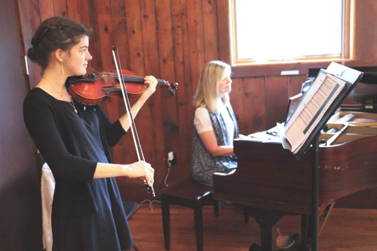 A girl plays violin at a wedding event, while a women plays piano in the background.